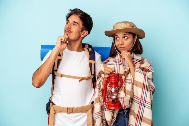 파란색 배경에 격리된 젊은 혼혈 등산객 부부는 의심스럽고 회의적인 표정으로 옆을 바라보고 있습니다.