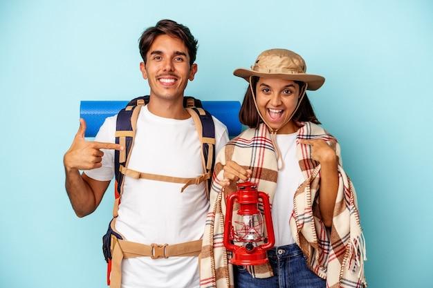 파란색 배경에 격리된 젊은 혼혈 등산객 부부는 자랑스럽고 자신감 있는 셔츠 복사 공간을 손으로 가리키는 사람