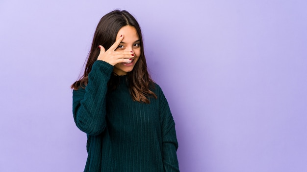Молодая испанская женщина смешанной расы изолировала моргание в камеру сквозь пальцы, смущенно закрывая лицо.