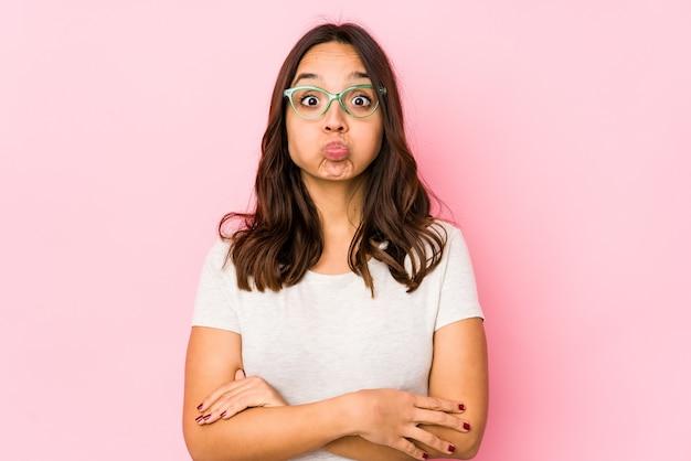 孤立した若い混血ヒスパニック系女性は頬を吹く、疲れた表情。顔の表情のコンセプトです。