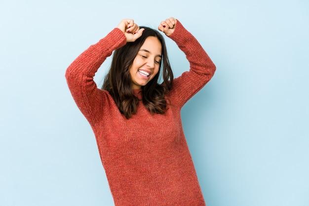 Молодая испанская женщина смешанной расы изолирована, празднует особый день, прыгает и поднимает руки с энергией.