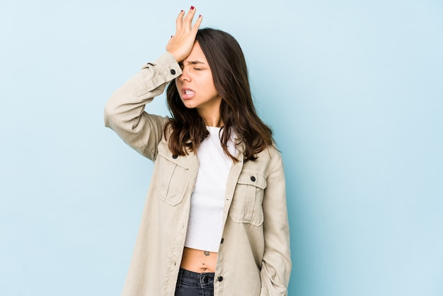 Young mixed race hispanic woman isolated forgetting something, slapping forehead with palm and closing eyes.