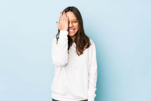 若い混合レースヒスパニック系女性が楽しんで分離された手のひらで顔の半分をカバーしています。