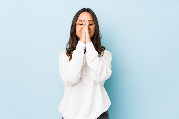 若い混合レースヒスパニック系女性が口の近くの祈りで手をつないで分離された、自信を持っています。