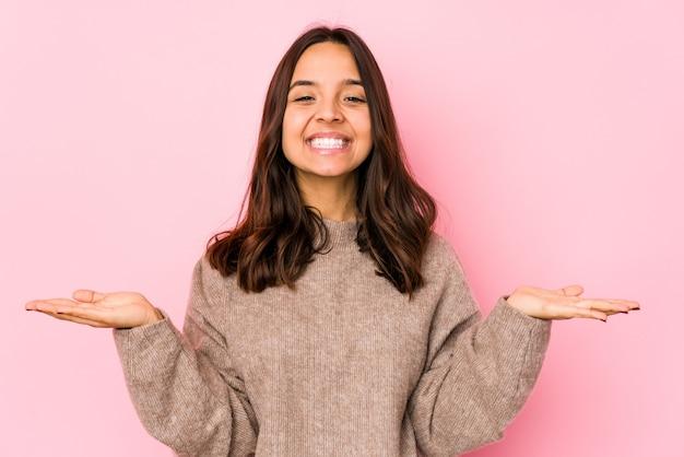 Изолированная молодая испанская женщина смешанной расы делает масштаб руками, чувствует себя счастливой и уверенной.