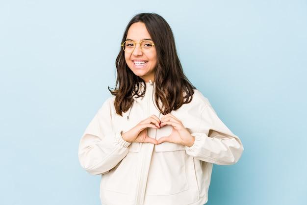 Испаноязычное женщина молодой смешанной расы изолировала усмехаясь и показывая форму сердца руками.