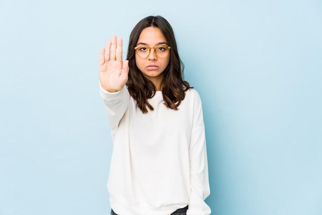 Молодая испанская женщина смешанной расы изолировала стоя с протянутой рукой, показывая знак остановки, предотвращая вас.