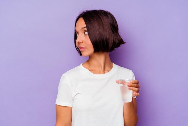 紫色の背景に分離された水のガラスを保持している若い混血は、笑顔、陽気で楽しい脇に見えます。 Premium写真