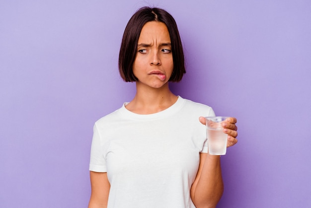 보라색 벽에 절연 물 한 잔을 들고 젊은 혼혈이 혼란스러워 의심스럽고 확신이 들지 않습니다.