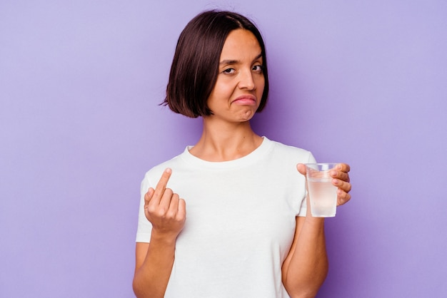 Young mixed race holding a glass of water isolated on purple background pointing with finger at you as if inviting come closer.