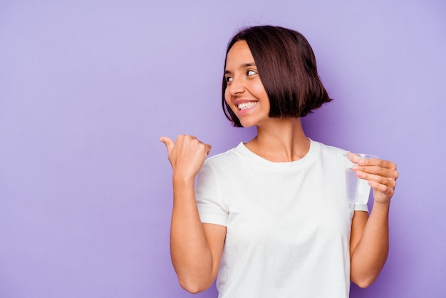Young mixed race holding a glass of water isolated on purple background points with thumb finger away, laughing and carefree.