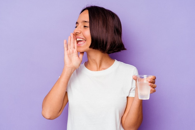 Young mixed race holding a glass of water isolated on purple background shouting and holding palm near opened mouth.
