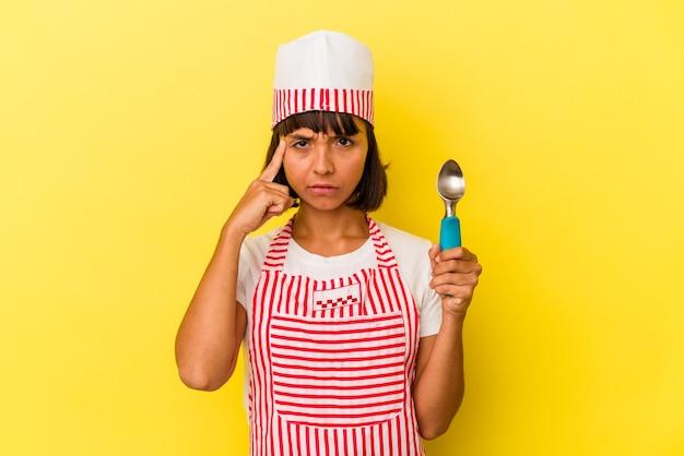 黄色の背景で隔離のアイスクリームスクープを保持している若い混血アイスクリームメーカーの女性
