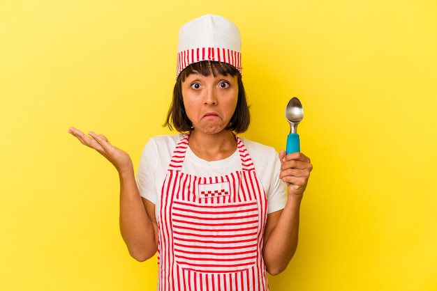 Молодая женщина-производитель мороженого смешанной расы, держащая совок мороженого на желтом фоне