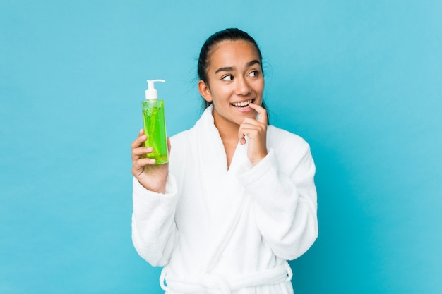 Young mixed race indian holding an aloe vera bottle relaxed thinking about something looking at a copy space.