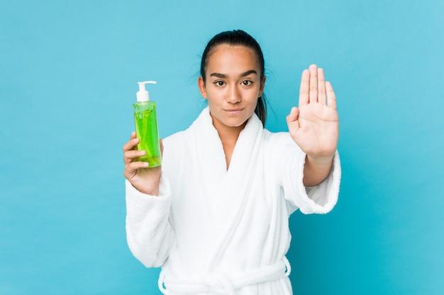 若い混血インド人が一時停止の標識を示す差し出された手で立っているアロエベラのボトルを持ってあなたを防ぎます。