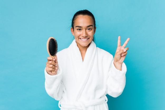 Молодой индеец смешанной гонки держа щетку для волос показывая номер два с пальцами.