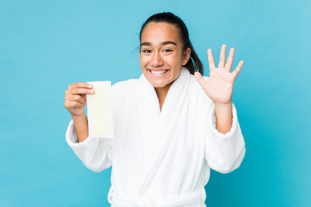 Young mixed race indian holding a depilatory band celebrating a victory or success