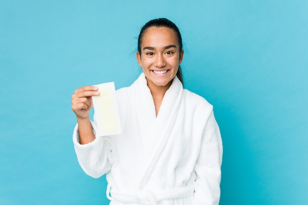 Young mixed race indian holding a depilatory band happy, smiling and cheerful.