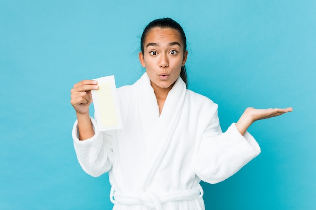 Young mixed race indian holding a depilatory band impressed holding copy space on palm.