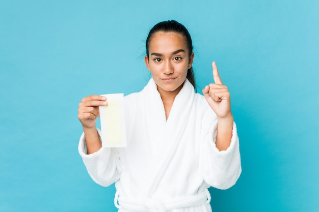 Young mixed race indian holding a depilatory band showing number one with finger.