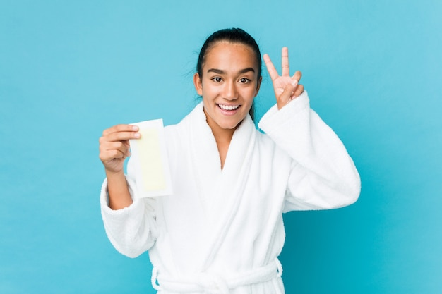 Young mixed race indian holding a depilatory band showing victory sign and smiling broadly.