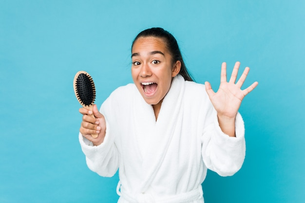 Young mixed race indian holding an hairbrush celebrating a victory or success