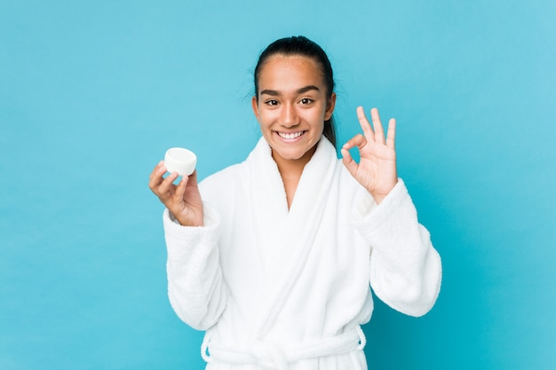 Young mixed race indian holding a moisturizer cheerful and confident showing ok gesture.