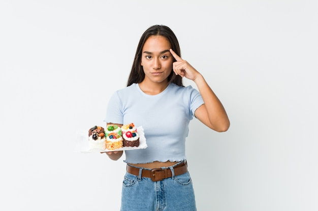 Young mixed race indian holding a sweet cakes pointing his temple with finger, thinking, focused on a task.