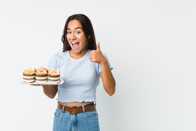 Young mixed race indian holding a sweet cakes smiling and raising thumb up