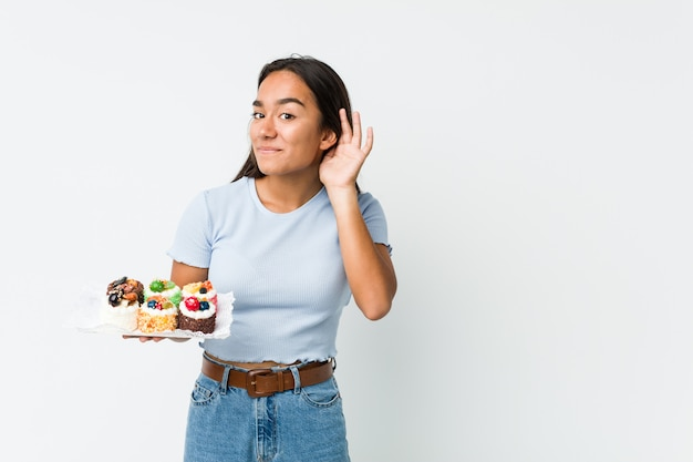 Young mixed race indian holding a sweet cakes trying to listening a gossip.