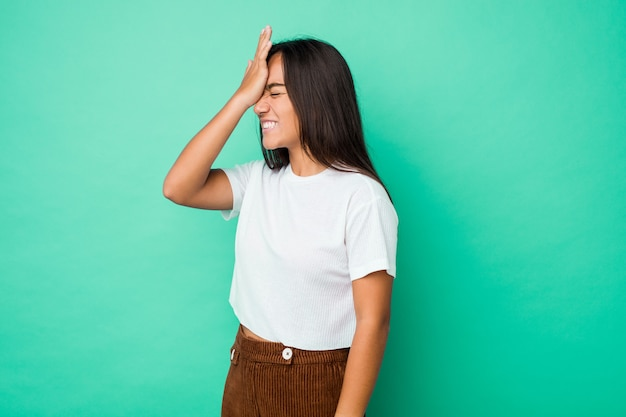 Young mixed race indian woman isolated forgetting something, slapping forehead with palm and closing eyes.