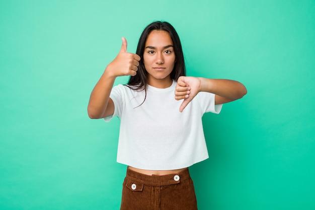 Молодая индийская женщина смешанной расы изолировала показывать большие пальцы руки вверх и большие пальцы руки вниз, трудно выберите концепцию