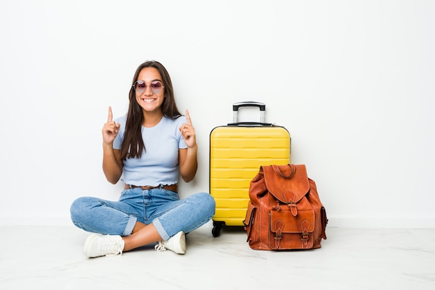 Young mixed race indian woman ready to go to travel indicates with both fore fingers up showing a blank space.