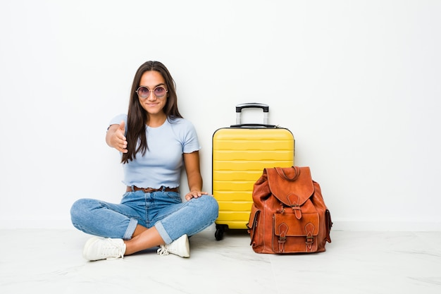 Young mixed race indian woman ready to go to travel stretching hand at camera in greeting gesture.