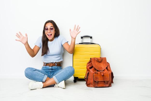 勝利または成功を祝って旅行に行く準備ができている若い混血のインド人女性、彼は驚いてショックを受けました。