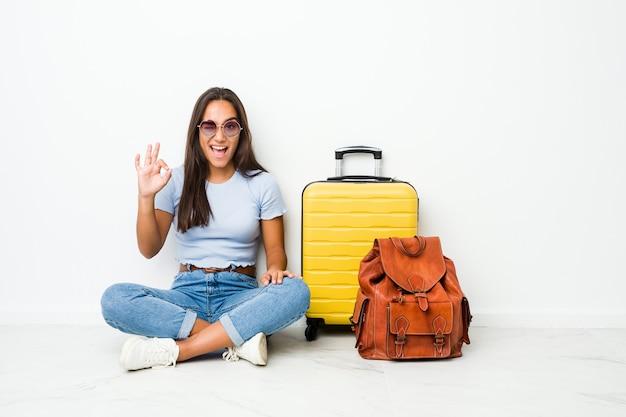 旅行に行く準備ができている若い混血インドの女性は目をまばたきし、手で大丈夫なジェスチャーを保持します。