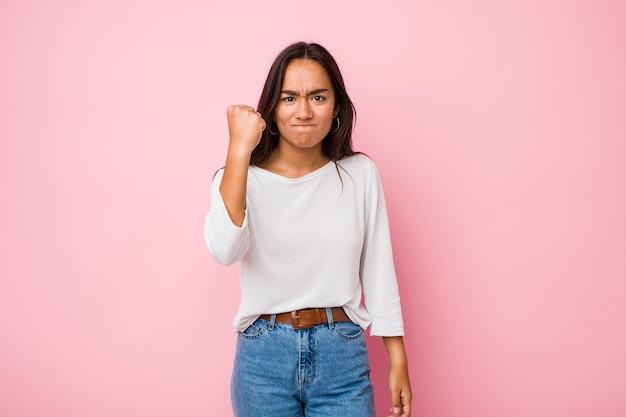 Молодая индийская женщина смешанной расы показывает кулак, агрессивное выражение лица.