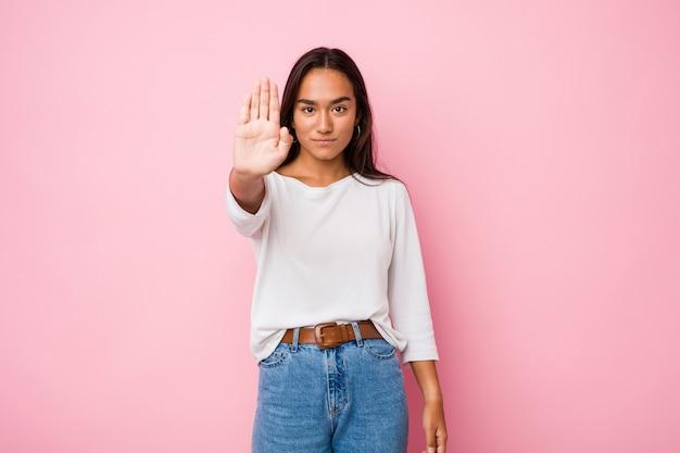 Женщина молодой смешанной гонки индийская стоя при протягиванная рука показывая знак стопа, предотвращая вас.