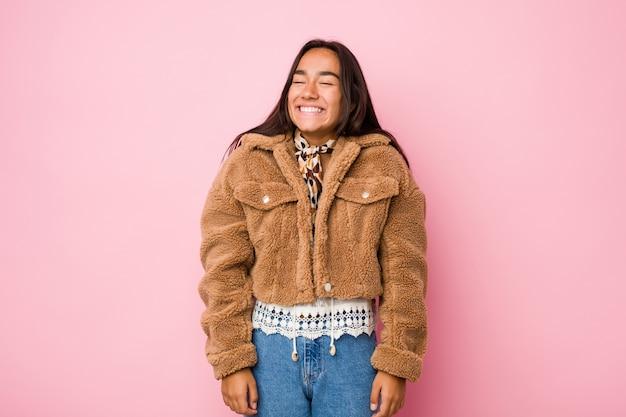 短い羊皮のコートを着た若い混血のインドの女性は笑って目を閉じ、リラックスして幸せを感じます。