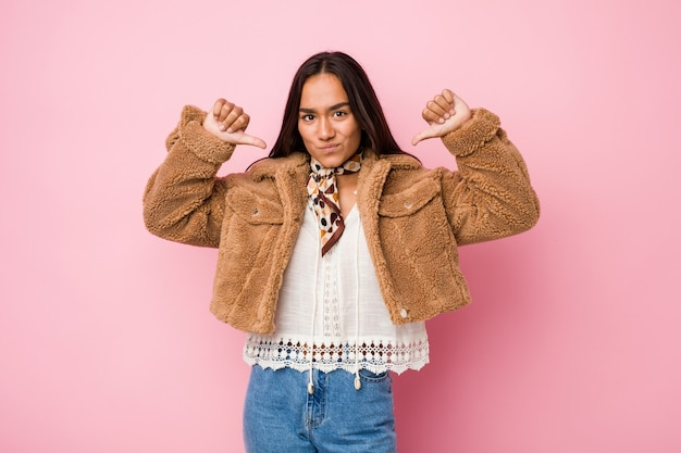 Young mixed race indian woman wearing a short sheepskin coatfeels proud and self confident, example to follow.