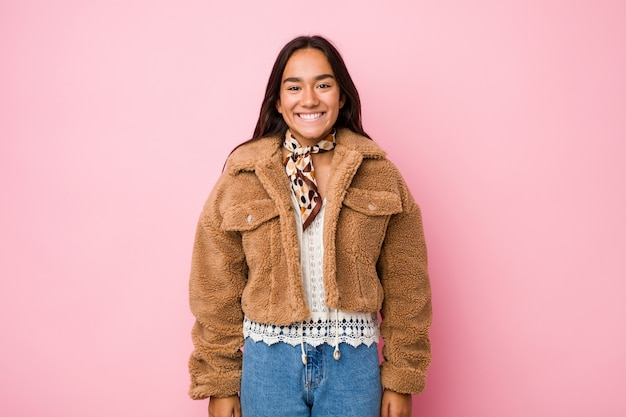 Young mixed race indian woman wearing a short sheepskin coathappy, smiling and cheerful.