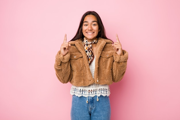 Young mixed race indian woman wearing a short sheepskin coatindicates with both fore fingers up showing a blank space.