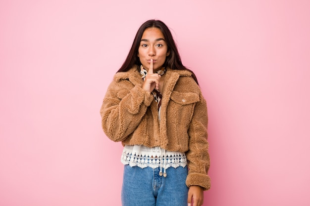 Young mixed race indian woman wearing a short sheepskin coatkeeping a secret or asking for silence.
