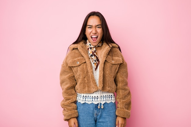 Young mixed race indian woman wearing a short sheepskin coatscreaming very angry and aggressive.