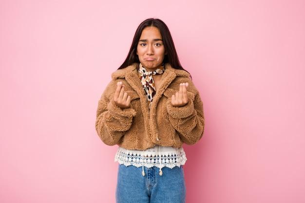 Young mixed race indian woman wearing a short sheepskin coatshowing that she has no money.