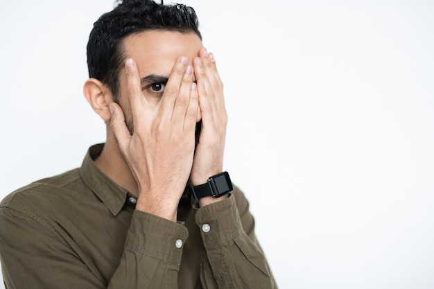 Young mixed-race male employee covering his face by hands and looking at you by one eye between fingers