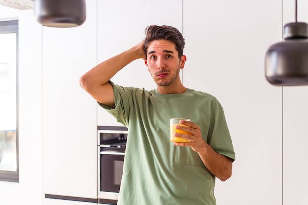 Young mixed race man drinking orange juice in his kitchen being shocked, she has remembered important meeting.