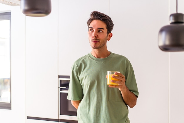 Young mixed race man drinking orange juice in his kitchen confused, feels doubtful and unsure.