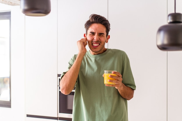 Young mixed race man drinking orange juice in his kitchen covering ears with hands.